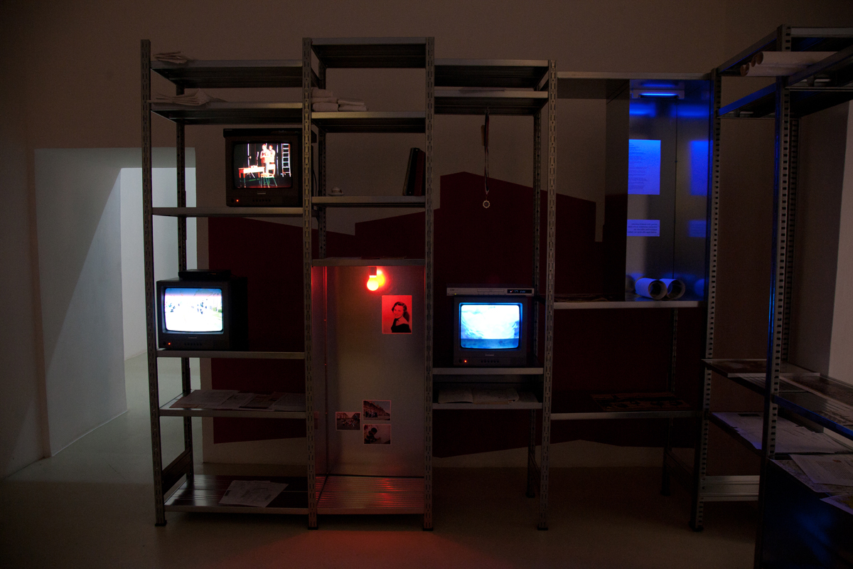 Rosas: The Trilogy, (Derby-The Attic), 2012, galvanized aluminum shelf, cctv monitors, photos, mixed media